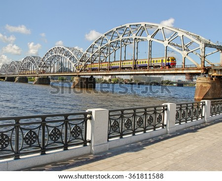 Railway bridge with two trains across river Daugava in Riga. - stock photo