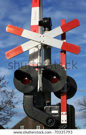 Railway crossing sign with lights underneath.  This is for a road traffic and to warn it of when a train is coming. The mechanics are set against a blue sky.