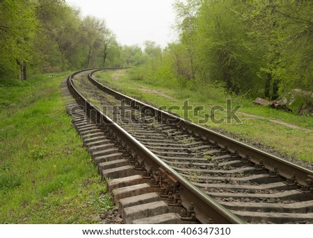 railway goes to horizon in green landscape - stock photo