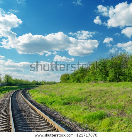 railway goes to horizon in green landscape under blue sky with clouds - stock photo
