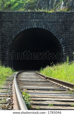 Railway going into ancient tunnel - stock photo