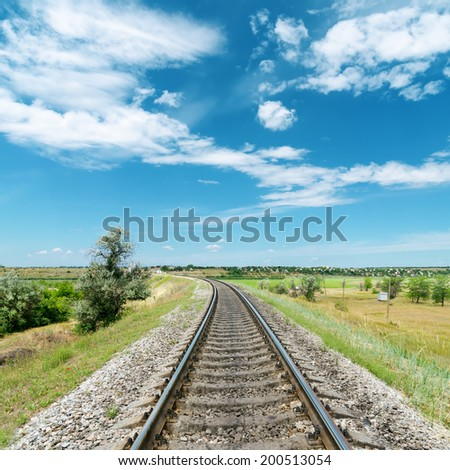railway in green landscape and white clouds in blue sky - stock photo