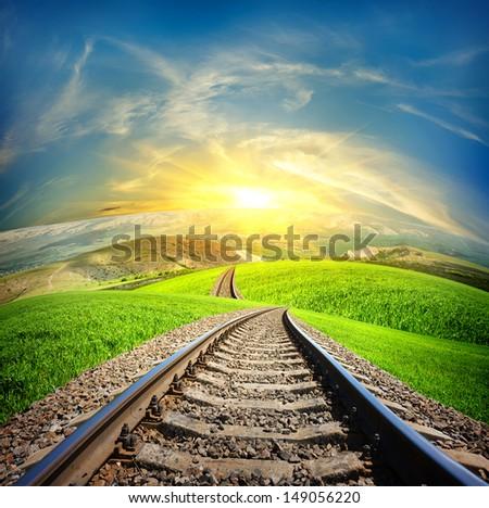 Railway in mountain fields in the sunlight - stock photo