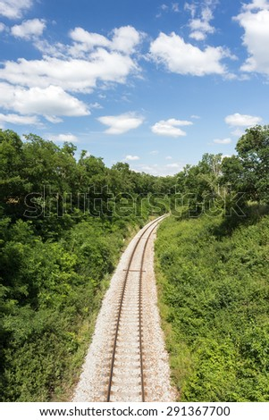 Railway in summer nature. Blue sky with white clouds - stock photo