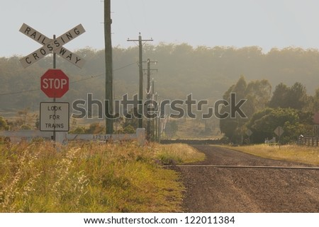 Railway level crossing with no boom gates in morning light outside toowoomba rural australia - stock photo