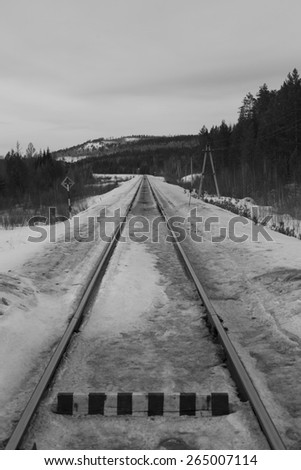 Railway level crossing with warning sign. black and white photo - stock photo