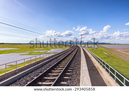 railway on bridge cross meadow and water - stock photo