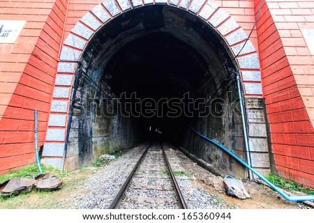 Railway Railroad tracks and tunnel and train - stock photo