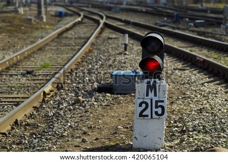 Railway semaphore burning red light on a background of a rail locomotive and sunny day - stock photo