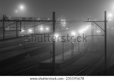 Railway station at a foggy night. - stock photo