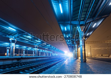 Railway station at night. Train platform in fog. Railroad in Donetsk.