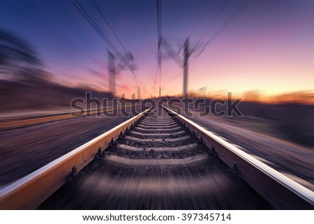 Railway station on the background of blue sky at beautiful sunrise with motion blur effect. Railroad in Ukraine.  - stock photo