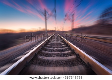 Railway station on the background of blue sky at beautiful sunrise with motion blur effect. Railroad in Ukraine.