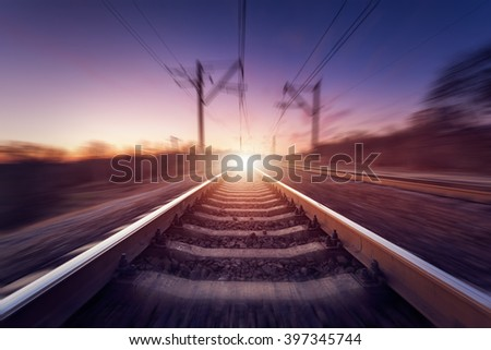 Railway station on the background of blue sky at beautiful sunrise with yellow light and motion blur effect. Railroad in Ukraine.