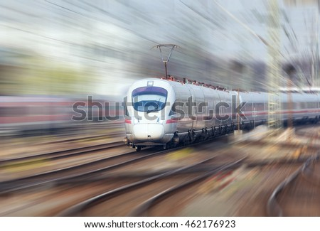 Railway station with modern high speed train in motion in the evening in Nuremberg, Germany. White train on the railroad track. Motion blur effect