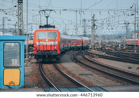 Railway station with modern red commuter train  in motion in the evening in Nuremberg, Germany. Red train on the railroad track with vintage toning - stock photo