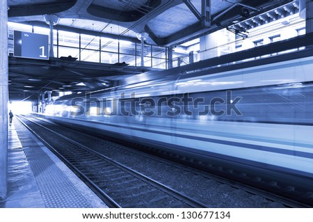 Railway station with short distance train in movement blue tone - stock photo