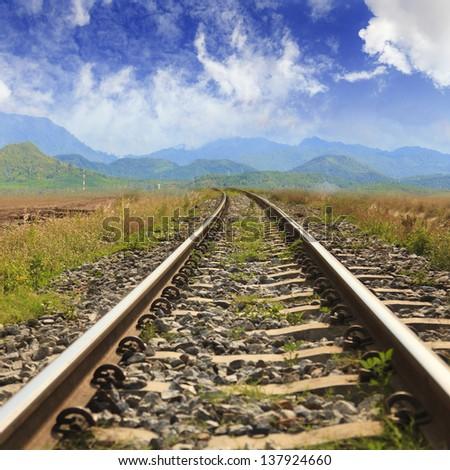 Railway through the mountains with blue sky - stock photo