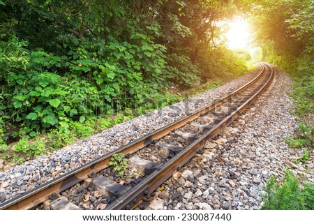 Railway track crossing rural landscape under evening sunset sky - stock photo