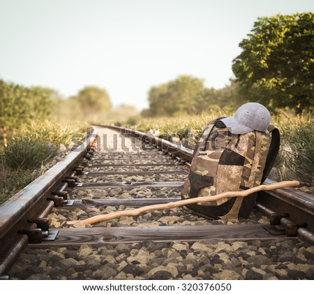 Railway track crossing rural landscape with travel backpack  - stock photo