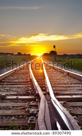 railway track leading to the sunset - stock photo