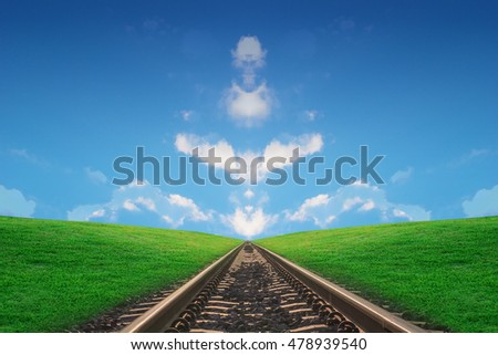 Railway track with green grass of hill and blue sky on the horizon