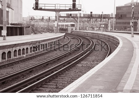 Railway Tracks and Train from Station Platform in Black and White Sepia Tone - stock photo