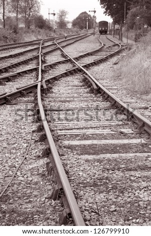 Railway Tracks and Train in Black and White Sepia Tone - stock photo