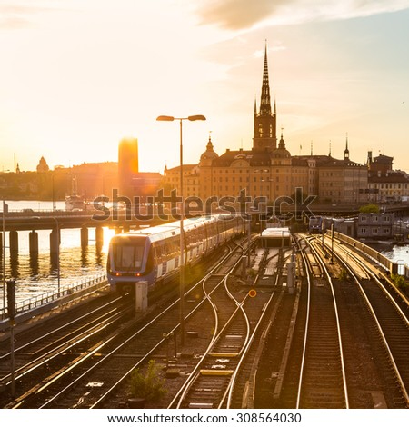 Railway tracks and trains near Stockholm's main train station in Norrmalm area, Stockholm, Sweden in sunset.  Silhouette of city hall and cathedral in background. Square composition. - stock photo
