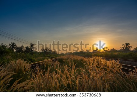 Railway tracks in a Rural Scene with Nice Sunrise and Grass Field - stock photo
