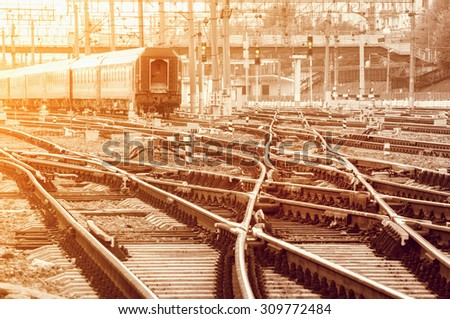 Railway tracks on the big station at sunset time. - stock photo