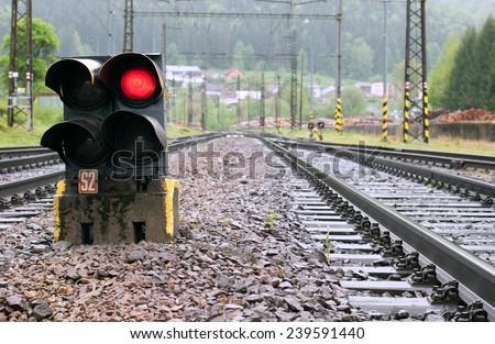 Railway tracks with red light semaphore - stock photo