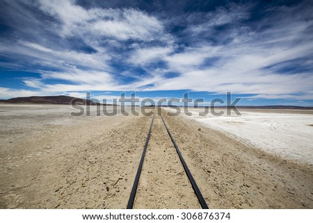 Railway with the desert, blue sky and the mountains in the background in Atacama Desert, Uyuni desert, Bolivia - stock photo
