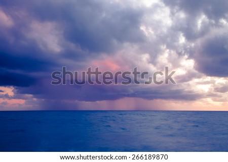 Rain above the sea. Sunset seascape. Toned. - stock photo