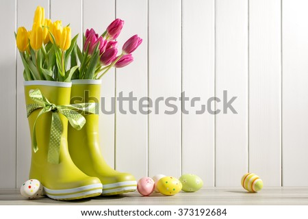 Rain boots, fresh tulips and easter eggs on wood background - stock photo