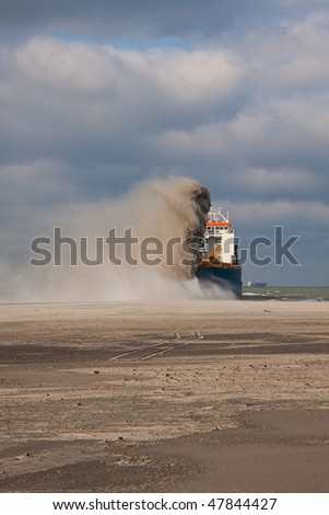 Rain-bowing sand on the beach - stock photo