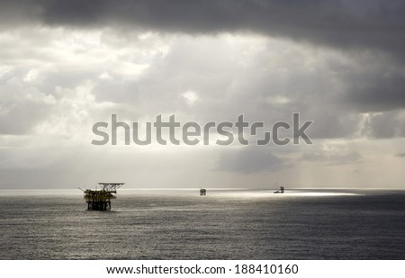 Rain clouds and oil-rigs in the midst of an open sea - stock photo