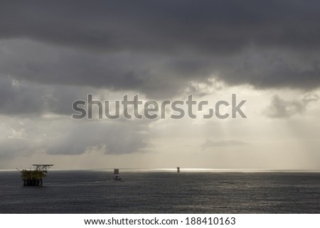 Rain clouds and oil-rigs in the midst of an open sea