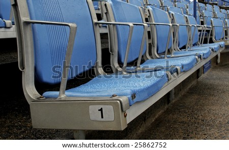 rain covered empty seats in a stadium.