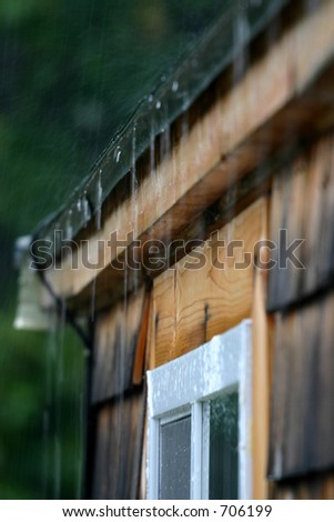 Rain dripping off the roof in a heavy storm. - stock photo
