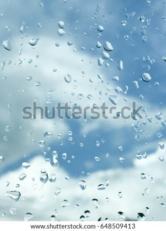 Rain drop on the window behind cloud background