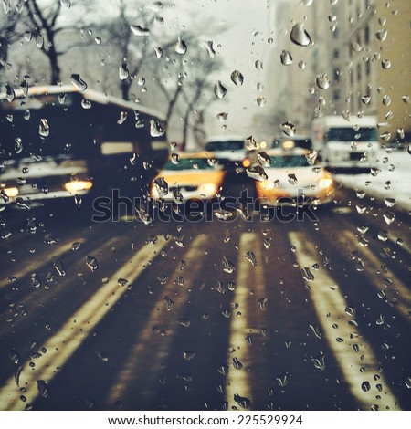Rain droplets on a car window looking into traffic. - stock photo