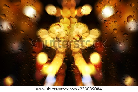 Rain droplets on a window glass pane with light trails of traffic.  - stock photo