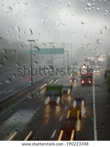 Rain droplets on a window glass pane with view of light trails of motor vehicle traveling on a wet and slippery highway after a heavy rainstorm. - stock photo