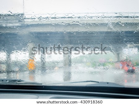 rain drops and car lights reflections through rear view mirror. summer day. Water drops on a car window. windscreen wipers - stock photo