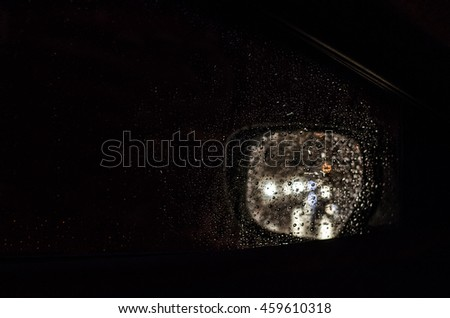 Rain drops and car lights reflections through rear view mirror. Water drops on a car window in the night - stock photo