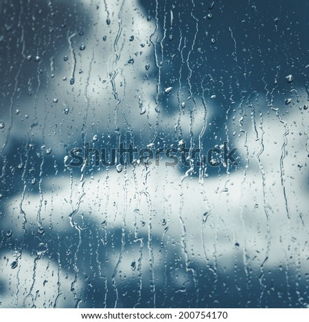 rain Drops and flows on window, blue sky with clouds on background - stock photo