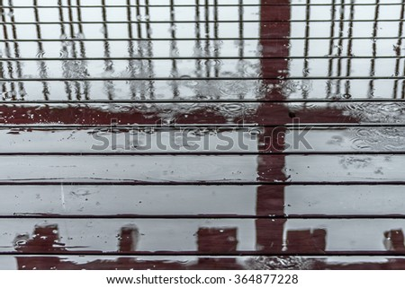 Rain drops dripping / splashing to red wood deck. Forming abstract designs and patterns against vertical bars, with selective focus. For abstract, vintage, grunge, weathered, backgrounds and textures. - stock photo