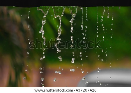 Rain drops fall continuously with blur green nature background. - stock photo
