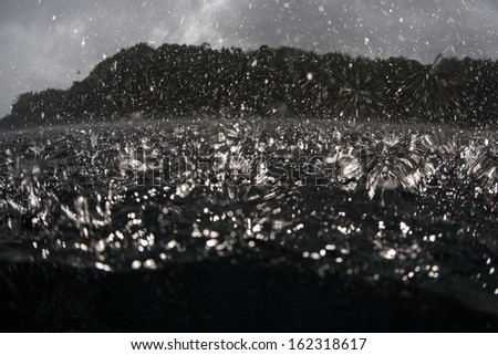 Rain drops fall on the surface of the water near the equator in the western Pacific Ocean.
